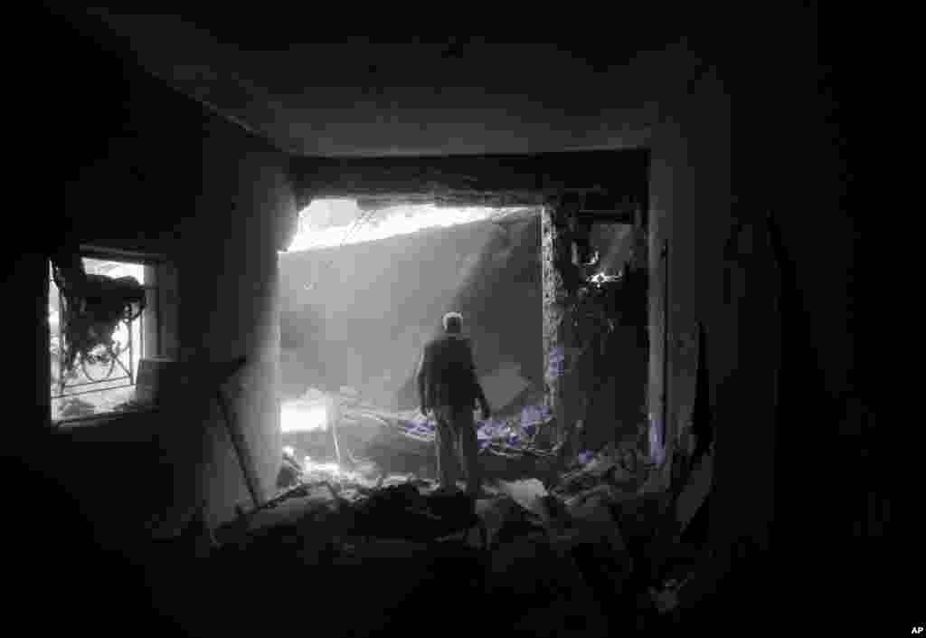 Thành viên của gia đình Shabat kiểm tra thiệt hại sau khi trở lại ngôi nhà bị phá hủy bởi các cuộc không kích của Israel tại thị trấn Beit Hanoun, phía bắc Dải Gaza, ngày 5/8/2014.