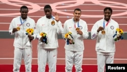 Gold medalist in the men's 4x400m relay, from left, Rai Benjamin (USA), Bryce Deadmon (USA), Michael Norman (USA) and Michael Cherry (USA) during the Tokyo 2020 Summer Olympic Games at Olympic Stadium.
