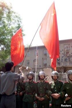 1999年5月10日,中国示威者在美国驻华使馆外面挥舞国旗。中国武警列队保护使馆。使馆墙壁被抗议美国轰炸中国驻南斯拉夫使馆的人用砖石砸得伤痕累累