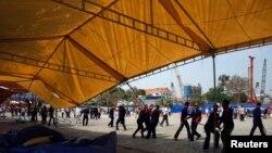 Bảo vệ và công nhân tháo dỡ các căn lều tại 1 khu trại bị người biểu tình chống chính phủ chiếm đóng ở Phnom Penh, 4/1/2014
