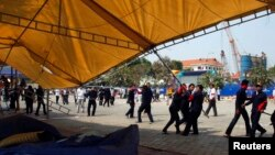 Para petugas keamanan dan pekerja berupaya merobohkan tenda yang digunakan untuk berkemah oleh para demonstran anti-pemerintah di Phnom Penh (4/1).