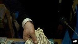 貨幣交易所的一名在里昂的僱員星期五擺出美元和20歐元的貨幣