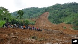 Cư dân và lực lượng cứu hộ xem xét hiện trường vụ đất lở chôn vùi nhà cửa ở làng Jemblung, Trung Java, Indonesia.