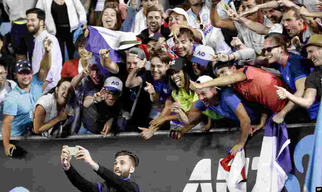 France's Benoit Paire takes selfie with his supporters as he celebrates after defeating Italy's Fabio Fognini in their second round match at the Australian Open tennis championships in Melbourne, Australia.