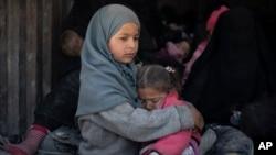 Seorang anak perempuan memeluk adiknya di kota Baghouz, Suriah timur dalam upaya evakuasi dari daerah terakhir ISIS di Suriah 20 Februari lalu (foto: ilustrasi).