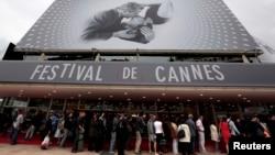 "Para pengunjung antri untuk memasuki gedung ""The Festival Palace"" yang dihiasi poster raksasa Festival Film Cannes ke-66 di Cannes (15/5). Perhiasan senilai $1,4 juta yang akan dipinjamkan kepada para bintang Festival FIlm tersebut dikabarkan raib dari kamar hotel yang dihuni pegawai perempuan perusahaan perhiasan Swiss, Choppard."