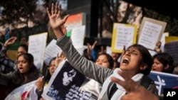 FILE - An Indian woman shouts slogans during a protest outside police headquarters against alleged police negligence in the murder and suspected rape of a woman in New Delhi, India, Jan. 13, 2015.
