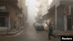 FILE - A man runs while pointing at a site hit by what activists said were airstrikes by forces loyal to Syria's President Bashar al-Assad in Raqqa, eastern Syria, which is controlled by the Islamic State, Nov. 27, 2014.