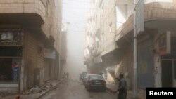 拉卡市有人奔跑,手指一处遭受轰炸的地方,据说是被忠于叙利亚总统的部队轰炸的