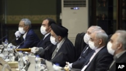 In this photo released by the official website of the Office of the Iranian Presidency, cabinet members wearing face masks and gloves attend their meeting in Tehran, Iran, Wednesday, March 18, 2020.