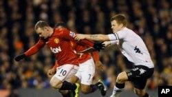 Pemain Fulham John Arne Riise (kanan) berebut bola dengan pemain Manchester United Wayne Rooney (foto: dok).