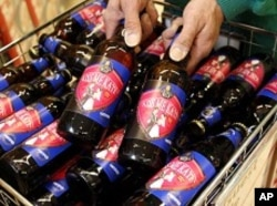 "A worker poses with bottles of ""Kiss Me Kate"" ale at a Morrisons supermarket in Leicester."