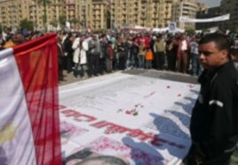 Mourners throw roses and pray over the names of some of those killed in Egypt's revolution, at a makeshift memorial in Tahrir Square, Cairo, February 12, 2011