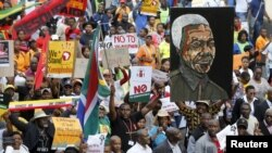 FILE - Demonstrators carry placards during a march against xenophobia in downtown Johannesburg, April 23, 2015.