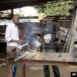 Elhadji Moctar Gueye stands beside one of his employees at his metallic workshop in Dakar, December 19, 2011.