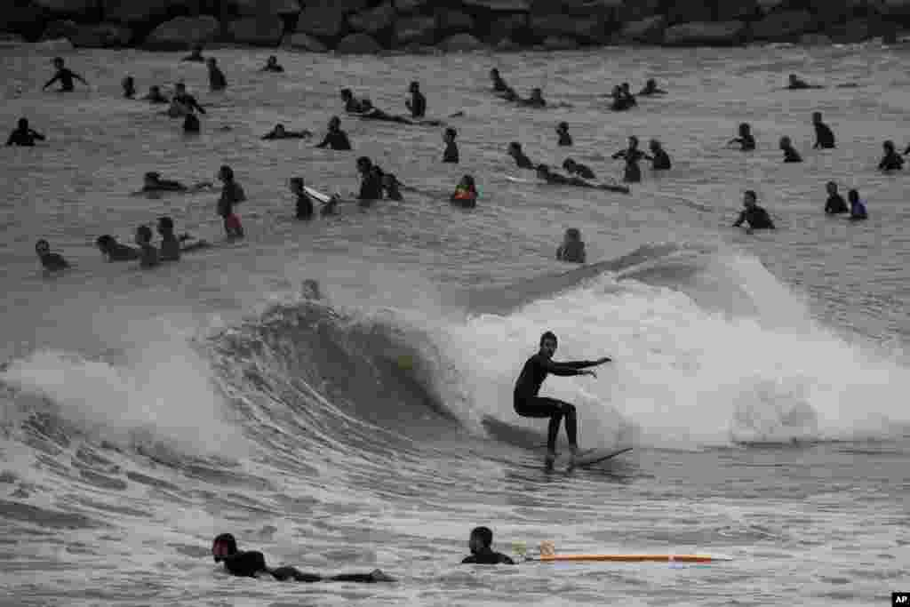People surf on a beach reopened for sport activities after the coronavirus lockdown in Barcelona, Spain, May 9, 2020.