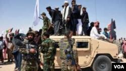 Des militants talibans afghans se tiennent debout sur un véhicule blindé de l'Armée nationale afghane (ANA) alors qu'ils célèbrent un cessez-le-feu le troisième jour de l'Aïd dans le district de Maiwand dans la province de Kandahar le 17 juin 2018.