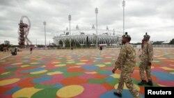 Tentara dari Resimen Royal Scottish berjalan melintasi Stadion Olimpiade di Stratford, sebelah timur London (17/7). Pemerintah Inggris mengerahkan 13.500 lagi tentaranya untuk menjaga keamanan saat berlangsungnya Olimpiade.
