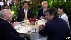FILE - President Donald Trump, third from right, and first lady Melania Trump, hidden at left, sit down to dinner with Japanese Prime Minister Shinzo Abe, third from left, and his wife Akie Abe, right, at Mar-a-Lago in Palm Beach, Florida, Feb. 10, 2017.