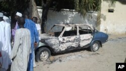 Men stand by a burned car following an attack by Boko Haram earlier this year.