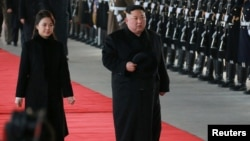 North Korean leader Kim Jong Un and wife Ri Sol Ju inspect an honor guard before leaving Pyongyang for a visit to China, in this Jan. 7, 2019 photo released by North Korea's Korean Central News Agency (KCNA) in Pyongyang, Jan. 8, 2019.