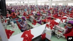 FILE PHOTO - Garment workers sew clothes in a factory as they wait for a visit by Prime Minister Hun Sen outside of Phnom Penh, Cambodia, Wednesday, Aug. 30, 2017.