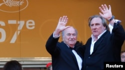 "FILE - Actor Gerard Depardieu (R) and then-FIFA President Sepp Blatter pose on the red carpet for the screening of the film ""United Passions"" at the 67th Cannes Film Festival, May 18, 2014."
