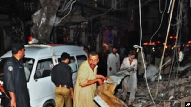 Pakistani people remove debris as they search for blast victims at the site of twin bomb blasts in Peshawar on June 11, 2011.
