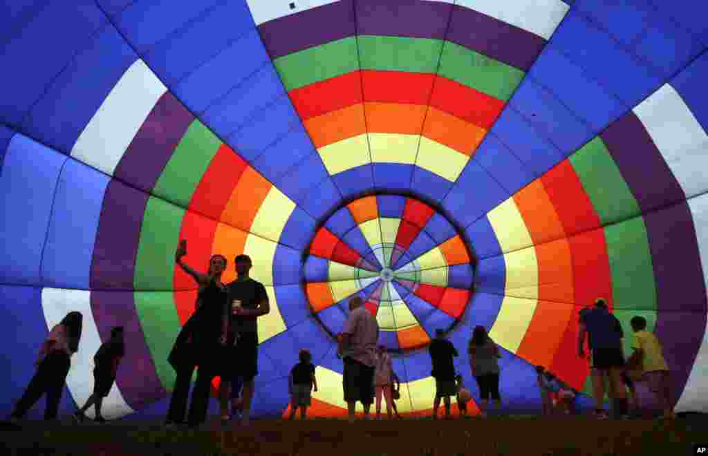 People walk around inside a partially inflated hot air balloon at the 32nd annual OuickChek New Jersey Festival of Ballooning in Readington, New Jersey, USA.