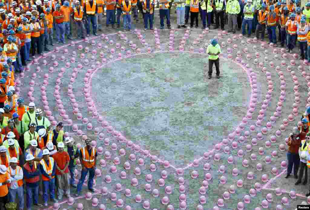 Construction workers from EMCOR Dynalectric wait to put on pink hard hats and be part of a giant pink ribbon formation to promote the start of Breast Cancer Awareness Month, at the UC San Diego Jacobs Medical Center construction site in La Jolla, California, Sept. 30, 2014.