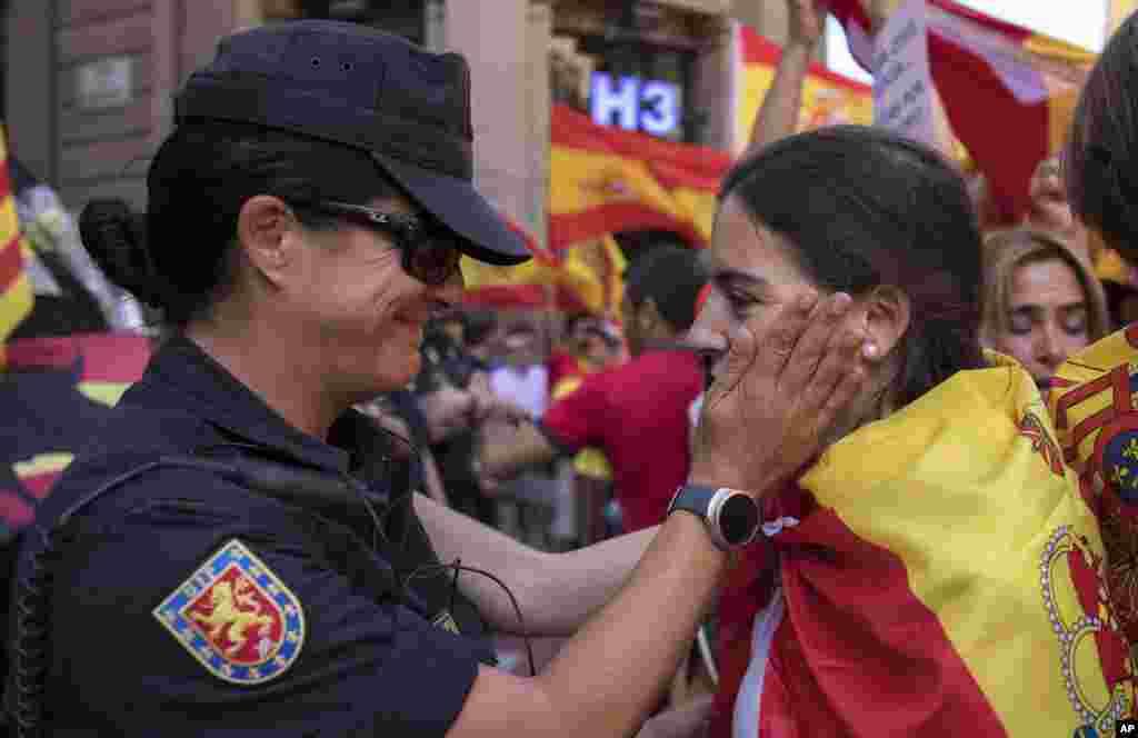 ប៉ូលិសអេស្ប៉ាញនិយាយជាមួយនឹងក្រុមបាតុករក្នុងពេលបាតុកម្មមួយប្រឆាំងនឹងការទាមទាររបស់រដ្ឋាភិបាលតំបន់ Catalonia សម្រាប់ការបំបែករដ្ឋចេញពីប្រទេសអេស្ប៉ាញ នៅក្នុងក្រុង Barcelona ប្រទេសអេស្ប៉ាញ។