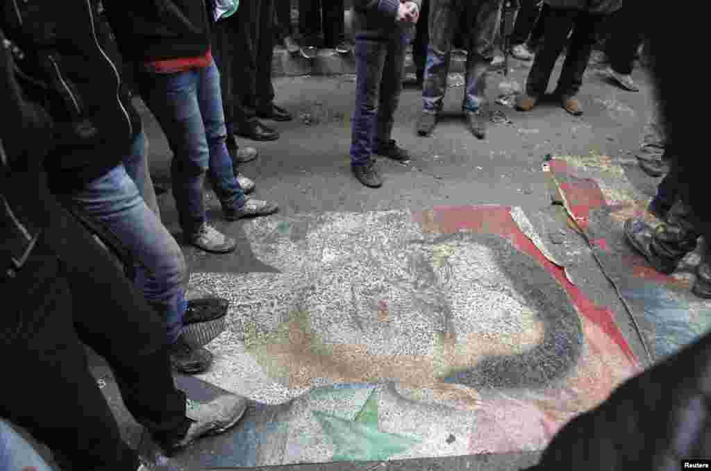 Demonstrators step on a picture of Syria's President Bashar al-Assad during a protest against his regime in Aleppo's Bustan al-Qasr district, January 4, 2013.