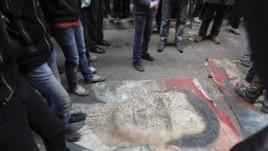 Demonstranti gaze po slici predsednika Bašara al-Asada, tokom protesta protiv njegovg režima u Alepu, 4. januara 2013.