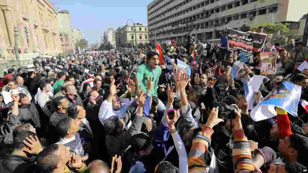 'Yan Sanda da mutane sun yi cincirindo a gaban ofishin da aka lalata bayan da bom ya fashe a cikin birnin Al-kahira, Junairu 24, 2014.