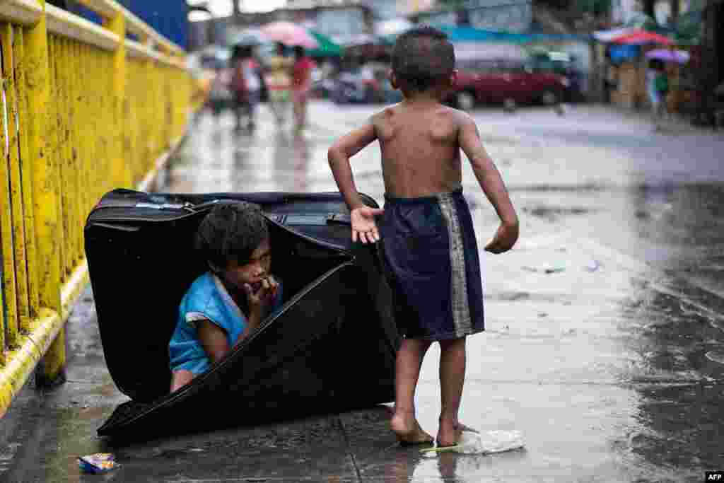 A boy hides in a suitcase at the Divisoria market in Manila, the Philippines.
