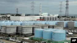 In this Oct. 12, 2017, photo, ever-growing amount of contaminated, treated but still slightly radioactive, water at the wrecked Fukushima Dai-ichi nuclear plant is stored in about 900 huge tanks, including those seen in this photo taken during a plant tour at Fukushima Daiichi Nu