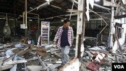 Seorang warga memeriksa pabrik sutera yang hancur di provinsi Surin, Thailand setelah bentrokan senjata militer kedua negara di perbatasan.