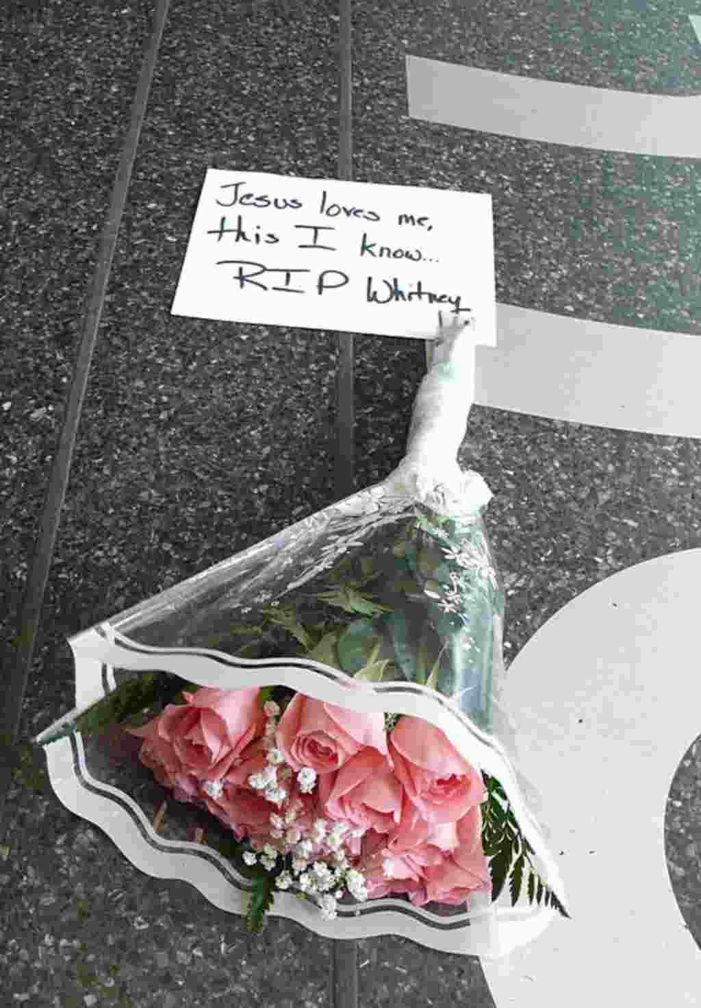 """A bouquet of pink roses placed at the entrance to Harlem's Apollo Theater in New York bears lyrics from the last song music superstar Whitney Houston ever sang in public, """"Yes, Jesus Loves Me."""" Houston, 48, died February 11, 2012 in Los Angeles. (AP)"""