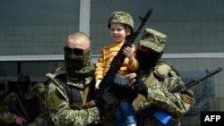 Rusya yanlısı militanlar ele geçirdikleri son kentde bir çocukla poz verirken