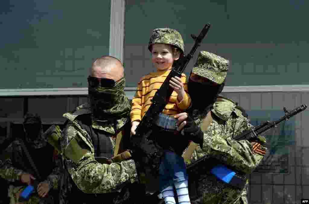 Pro-Russian armed men in military fatigues pose for a photograph with a child as they stand guard outside a regional administration building seized overnight by pro-Russian separatists, in the eastern Ukrainian city of Kostyantynivka.