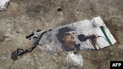 Bức hình của ông Gadhafi rơi xuống đất trong khu dinh cơ của ông ở Tripoli