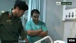 Gambar dari televisi pemerintah Libya ini menunjukkan Khamis Gaddafi (kiri) masih hidup, dan sedang mengunjungi warga Libya yang terluka di sebuah rumah sakit.