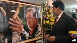 Presiden sementara Venezuela Nicolas Maduro berdiri di depan potret mendiang Presiden Hugo Chavez seusai upacara pengambilan sumpah secara simbolis (8/3).
