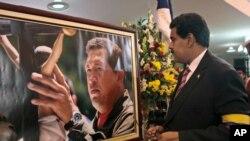 马杜罗星期五宣誓就任代理总统后站在查韦斯像前