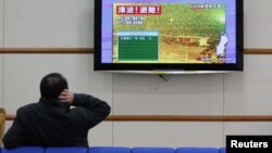 """A man scratches his head as he watches television showing live camera footage from Ishinomaki, Miyagi prefecture and an alert sign that reads,""""Tsunami! Evacuate!"""" at Nagano train station, central Japan December 7, 2012"""