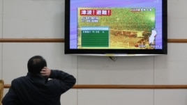 Un hombre lee sobre la alerta de tsunami tras un fuerte terremoto en el norte de Japón. La alerta fue levantada horas después.