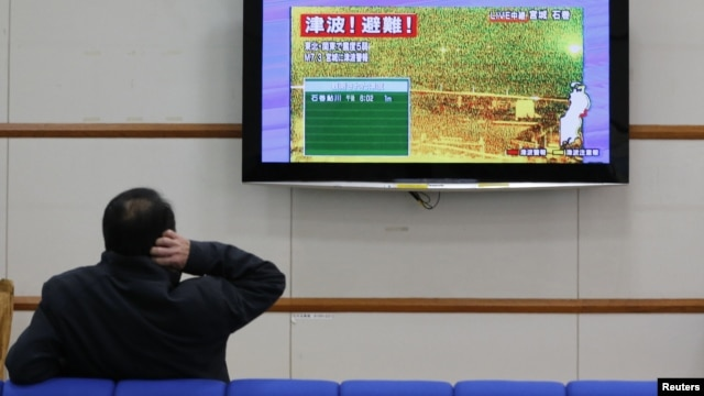 "A man scratches his head as he watches television showing live camera footage from Ishinomaki, Miyagi prefecture and an alert sign that reads,""Tsunami! Evacuate!"" at Nagano train station, central Japan December 7, 2012"
