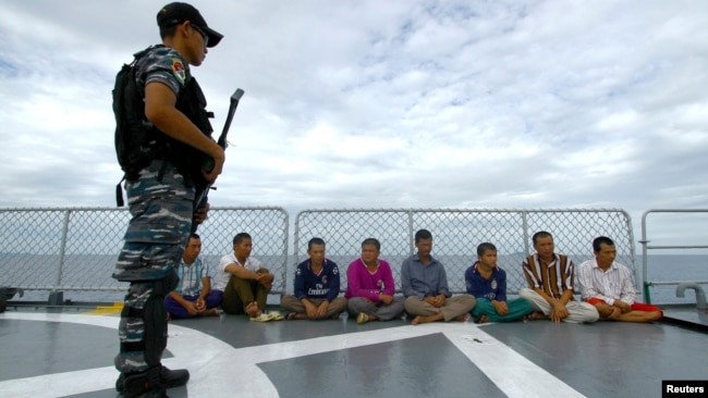 FILE - An Indonesian soldier stands guard near detained Vietnamese fisherman onboard Indonesian warship, KRI Barakuda 633, off the Natuna Sea in Anambas, Kepulauan Riau province, Dec. 5, 2014.