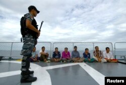 An Indonesian soldier stands guard near detained Vietnamese fisherman onboard Indonesian warship, KRI Barakuda 633, off the Natuna sea in Anambas, Kepulauan Riau province