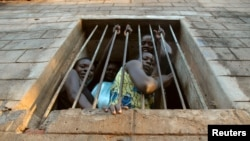Des prisonnières assises à la fenêtre de leur cellule dans la prison de Yei dans le sud du Soudan, 16 avril 2006.